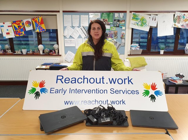 Managing director of Reachout.work Karen Lynch accepts Rapid IT's donation of laptops for the charity.