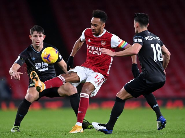 Pierre-Emerick Aubameyang of Arsenal is put under pressure by Ashley Westwood (R) and James Tarkowski of Burnley (L) during the Premier League match between Arsenal and Burnley at Emirates Stadium on December 13, 2020 in London, England.
