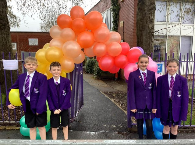 Welcome back! Some of the pupils with the 'welcome back' balloom arch at Burley'sSt Mary Magdalene's RC Primary School
