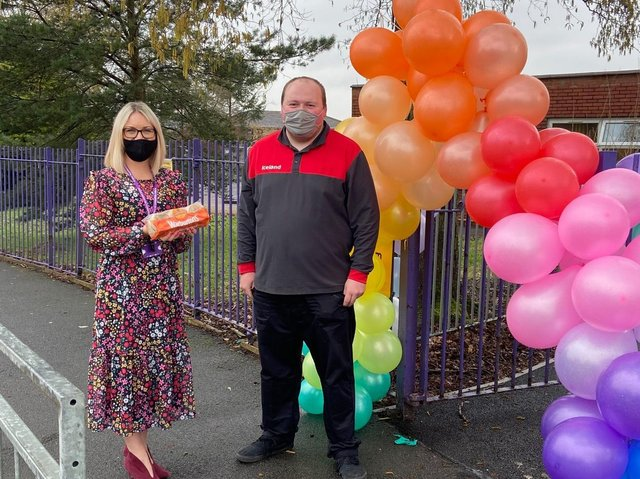 Iceland delivey driver Aaron Girling presents the crumpets to Sarah Ginn at Burnley's St Mary Magdalene's RC Primary School