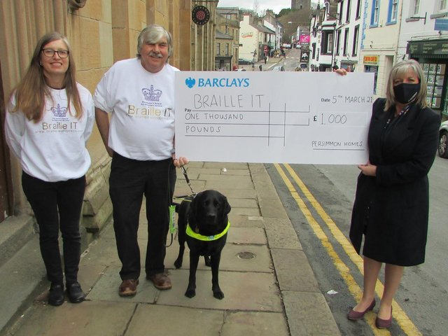(From left) Receiving Community Champions funding for Braille IT are Alison Hargeaves, Chris Tattersall and Goughy the dog with Persimmon Homes sales director Diane Finch outside the library in Clitheroe.