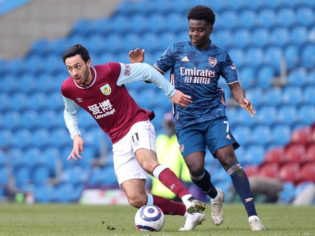 Dwight McNeil of Burnley is challenged by Bukayo Saka of Arsenal during the Premier League match between Burnley and Arsenal at Turf Moor on March 06, 2021 in Burnley, England.