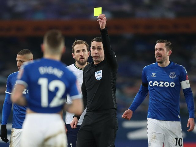 Everton's French defender Lucas Digne (front) is shown the yellow card by referee David Coote during the English FA Cup fifth round football match between Everton and Tottenham Hotspur at Goodison Park in Liverpool on February 10, 2021.