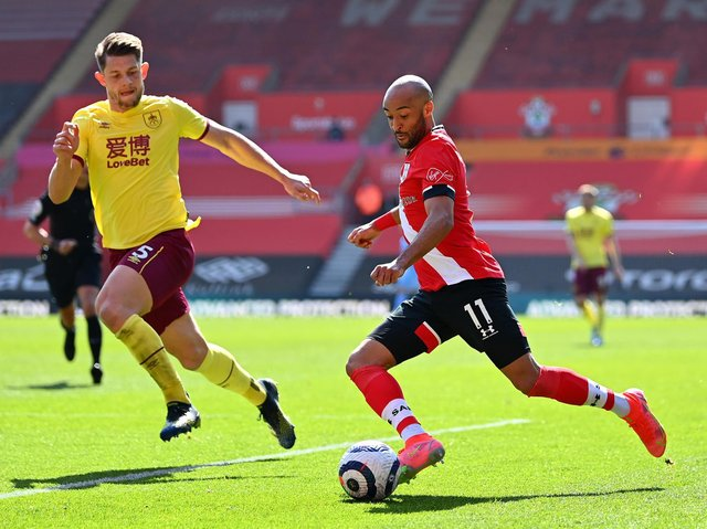 Nathan Redmond of Southampton crosses the ball under pressure from James Tarkowski of Burnley during the Premier League match between Southampton and Burnley at St Mary's Stadium on April 04, 2021 in Southampton, England.