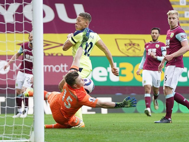 Burnley's English goalkeeper Bailey Peacock-Farrell (down) stops the ball next to Newcastle United's English striker Dwight Gayle (up) during the English Premier League football match at Turf Moor in Burnley, north west England on April 11, 2021.