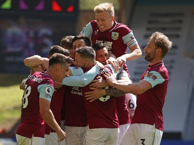 Burnley's English midfielder Ashley Westwood (R) is mobbed by teammates after scoring his team's fourth goal during the English Premier League football match between Wolverhampton Wanderers and Burnley at the Molineux stadium in Wolverhampton.
