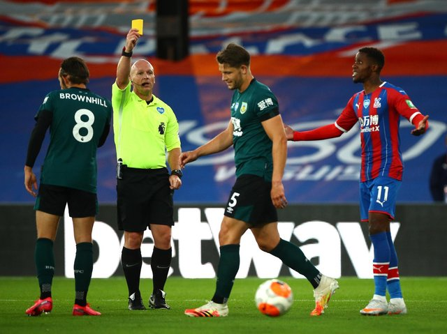 James Tarkowski of Burnley is shown a yellow card by referee Simon Hooper as Wilfried Zaha of Crystal Palace reacts during the Premier League match between Crystal Palace and Burnley FC at Selhurst Park on June 29, 2020 in London, United Kingdom.