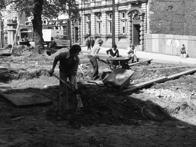 Men start work at Preston Parish Church, digging up ancient tombstones during landscaping