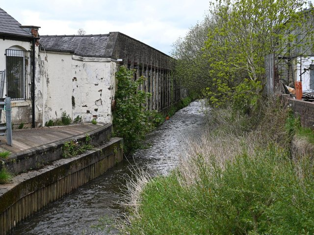 New Cut next to the mill affected by flooding. The  scheme would waterproof the wall on the bank of the beck.