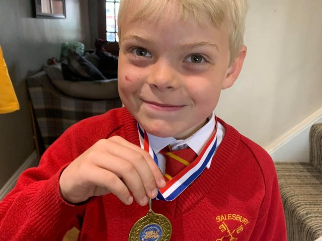 Alfie Holden proudly shows off his medal after completing the 100 laps challenge