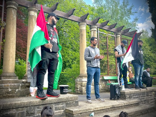 Local protestors bearing the Palestinian flag gather at Thompson Park in Burnley