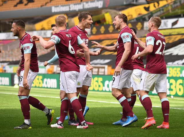 Chris Wood of Burnley celebrates with team mates after scoring their side's third goal and his hat trick during the Premier League match between Wolverhampton Wanderers and Burnley at Molineux on April 25, 2021 in Wolverhampton, England.