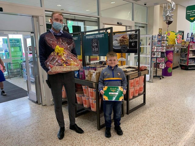 Alfie receives his award at Morrisons store in Todmorden from operations manager James