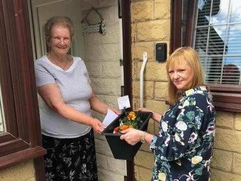 One of the nominated residents receives a window box made by children at Rosegrove Infant School in Burnley