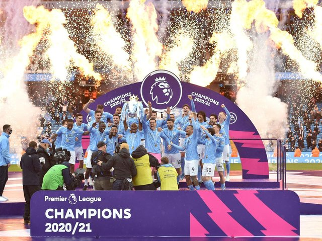Manchester City's Brazilian midfielder Fernandinho lifts the Premier League trophy during the award ceremony after the English Premier League football match between Manchester City and Everton at the Etihad Stadium in Manchester, north west England, on May 23, 2021.