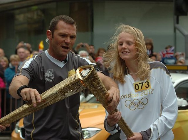 Elizabeth Greenwood has the torch lit before her route starts.