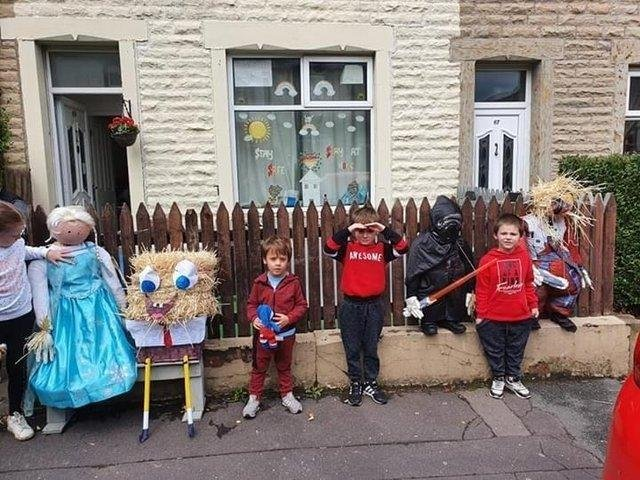 Proud youngsters show off the scarecrows they made for the Rosegrove Scarecrow Festival in 2020